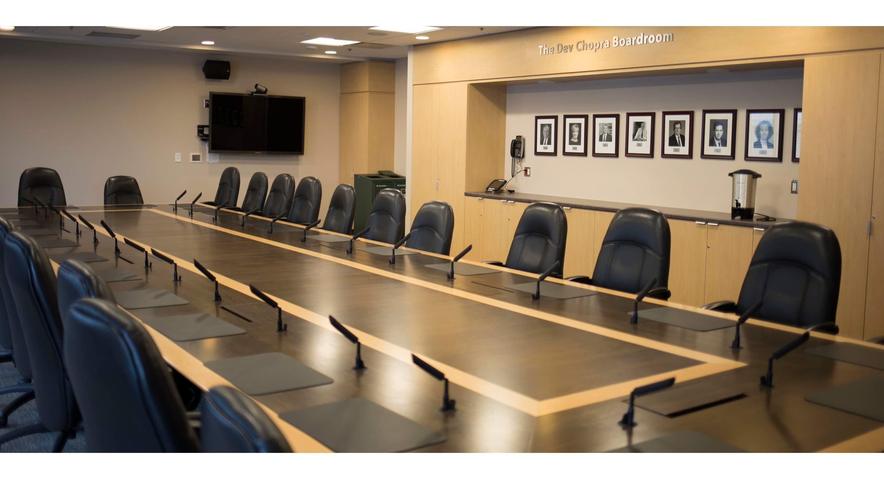 An image of the CAMH boardroom with a long table and many leather office chairs surrounding it.